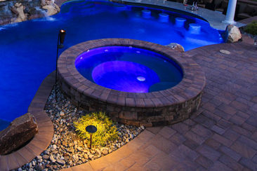 Raised spa with led lighting and custom pool side landscaping with river jack stone and low voltage path lighting.
