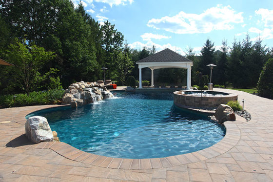 Free-form pool with water features such as a boulder waterfall, sun shelf, swim up bar, and raised
