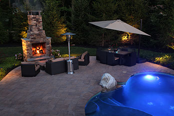 Outdoor fireplace next to in ground pool.